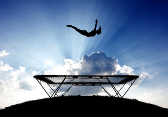 Wall Mural - silhouette of female gymnast on trampoline in sky