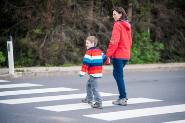 Mutter und Sohn überqueren Strasse