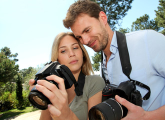 Couple looking at pictures through camera screen