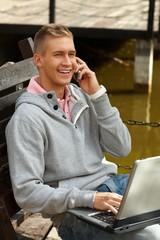 Young man on mobile smiling outdoor