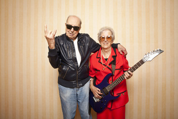 cool fashion elder couple with electric guitar
