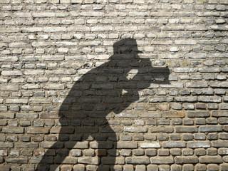 ombre de photographe sur mur de briques