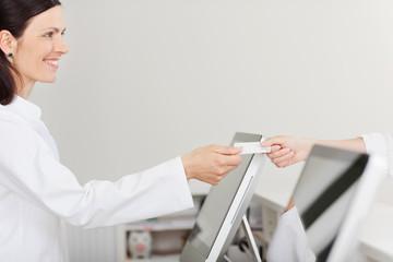 patientin überreicht gesundheitskarte am empfang