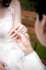 Groom putting a wedding ring on bride finger