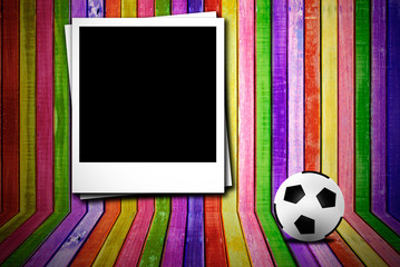 Photoframe and soccer ball on colorful empty wood advertisement