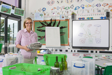 Smiling teacher standing with recyclables and bins in classroom