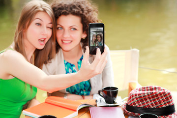 Two beautiful women photographing themselves with a smart-phone