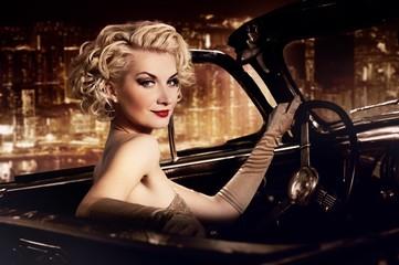 Woman in retro car against night city.