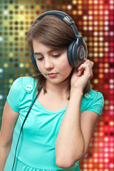 attractive teen girl with headphones on color  background .