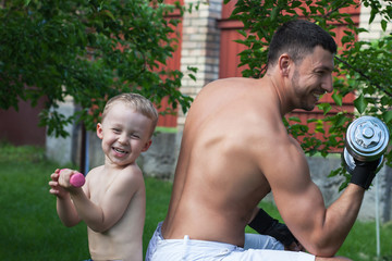 Father and son train with dumbbells