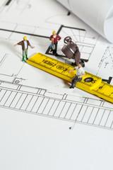 Männer arbeiten nach einem Bauplan.