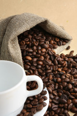 A sack of coffee beans and a cup, closeup
