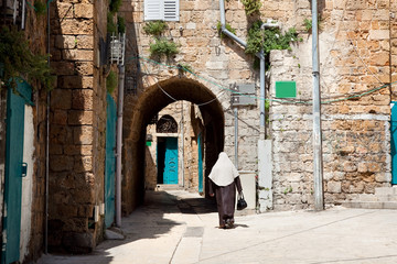 Muslim lady walking in a street of Akko