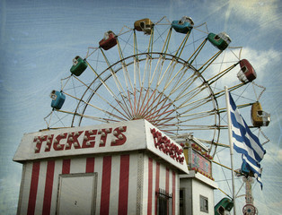 Aged and worn vintage photo of ferris wheel and ticket booth