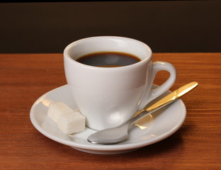 Coffee cup on wooden table on brown background