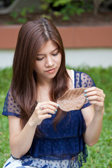 Asian woman looking at dried leaf