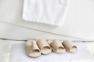 slippers and bath towel by the bathtub