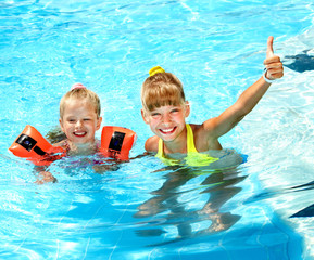 Child with armbands in swimming pool.