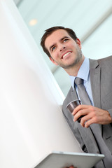 Portrait of businessman drinking coffee in hallway