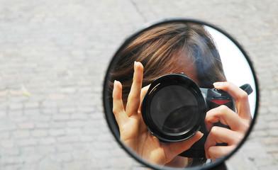 Riflesso di una fotografa nello specchietto di un motorino