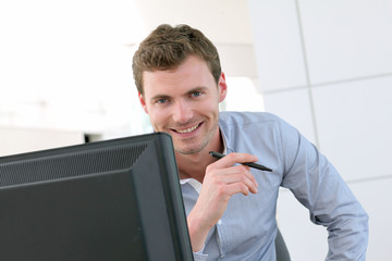 Handsome office-worker sitting at his desk