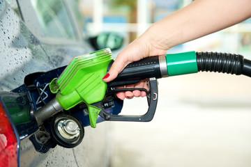 Frau tankt Auto an Tankstelle