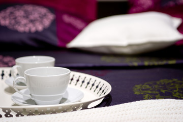 Two cups on a nice bed