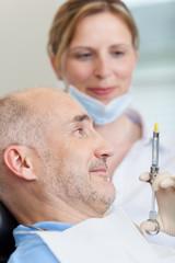 patient beim zahnarzt schaut auf spritze
