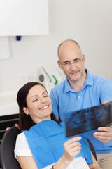 zahnarzt zeigt einer patientin ein röntgenbild
