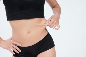 Femme tirant sur la peau de son ventre plat