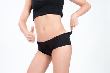 Femme au ventre plat montrant le résultat de son régime