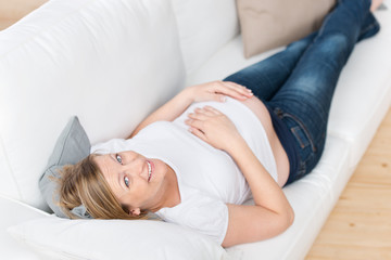 glückliche schwangere frau liegt auf dem sofa
