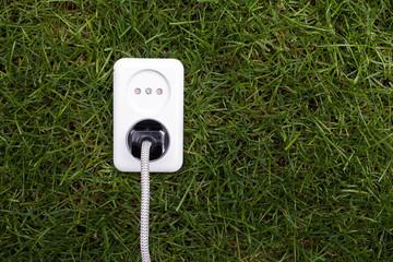 European power socket on grass. Energy concept