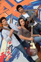 musical trio against graffiti wall