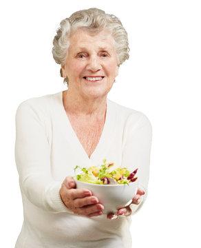 portrait of senior woman showing a fresh salad over white backgr