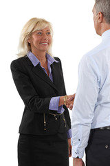 Two senior businesspeople shaking hands