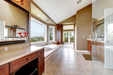 Large modern luxury new master bathroom in brown.