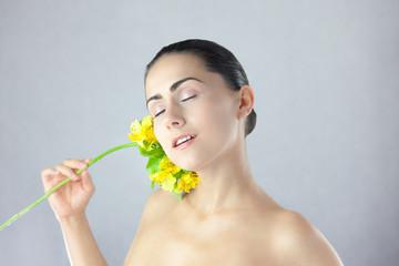 Fototapeta Piękna kobieta z żółtym kwiatkiem na srebrnym tle obraz