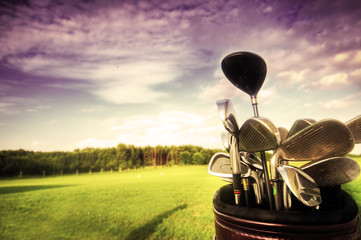 Foto auf Acrylglas Golf Golf gear, clubs at sunset on golf course