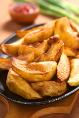 Homemade crispy fried potato wedges on metallic plate