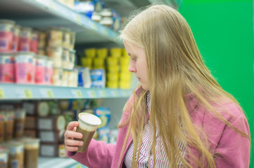 Young woman near shelves with milk deserts in supermarket
