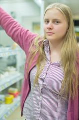 Young woman near shelves in supermarket