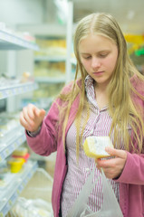 Young woman near shelves with cheese in supermarket