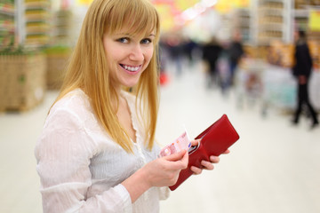 Happy girl gets money from her red purse in store