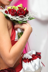 young bride hand holds bouquet of red roses