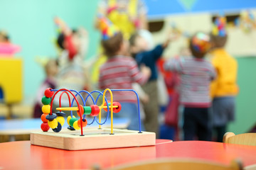 Colorful wooden toy stand at red table in kindergarten;
