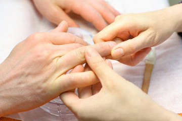 Female hands make manicure for man in beauty salon