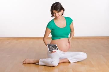 Schwangere sitzt auf dem Boden mit Ultraschallbild