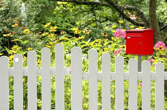 Briefkasten in rot am Zaun