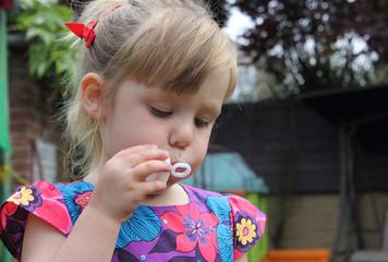 Cute girl blowing bubbles